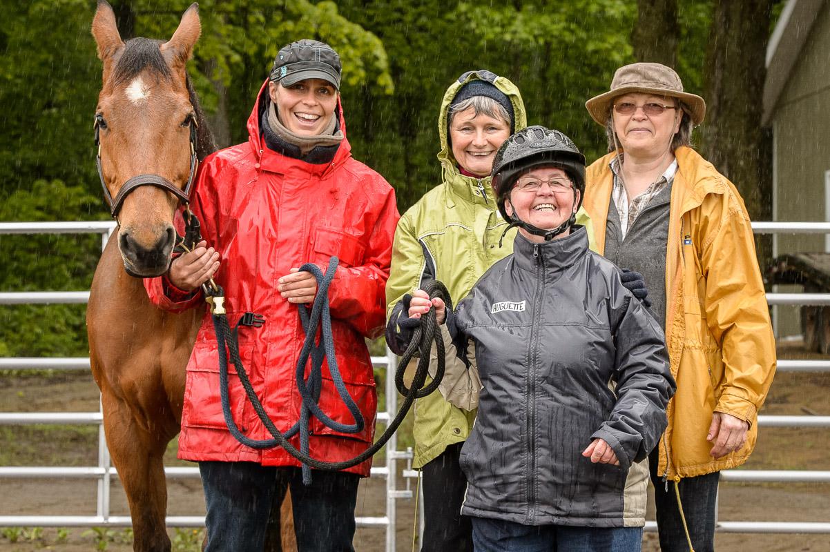 Tous posent fièrement! Derrière l'une des participantes, un cheval, Julie, intervenante en zoothérapie (manteau rouge), Marie bénévole de de l'APHP (manteau vert) et Louise, bénévole et propriétaire de l'un des chevaux.